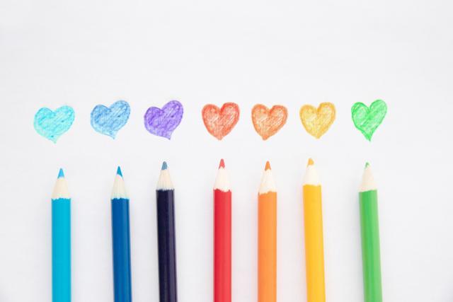 色とりどりのハートマークと色鉛筆