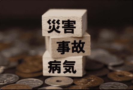 様々な生活リスクを積み重ねた積み木と小銭