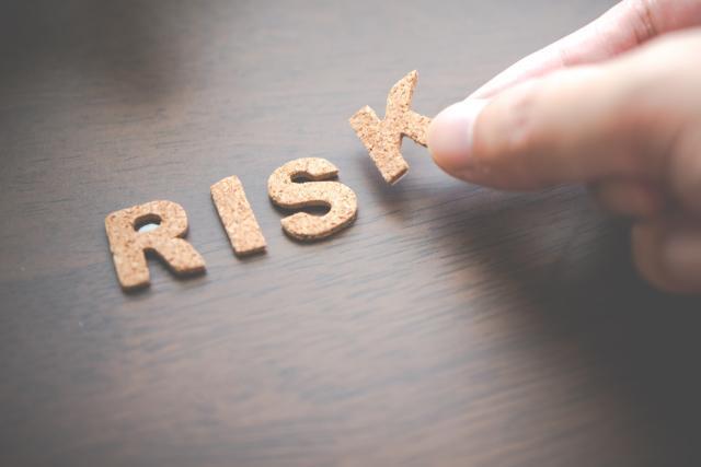 RISKの文字が置かれた机と手